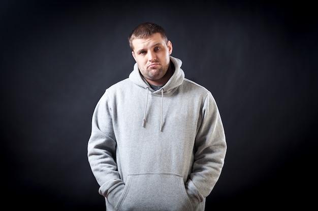 スポーツ用のグレーのスウェットシャツを着た若い黒髪の男は、病気になって悲しそうに見えることに腹を立てました