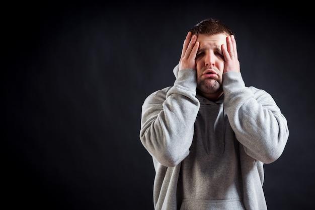 Молодой темноволосый мужчина в спортивной серой кофте страдает от головной боли