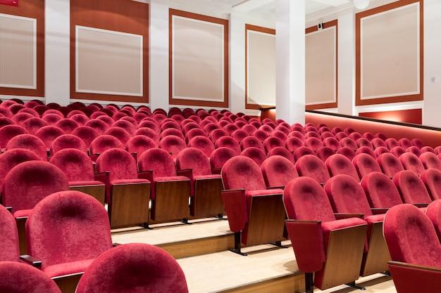 Вид с лестницы на ряды удобных красных стульев в театре