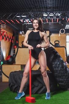 Молодая красивая спортивная стройная девушка в чёрном купальнике держит красный молоток.