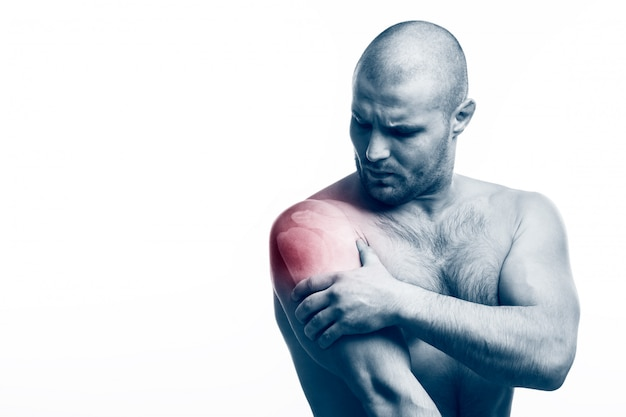 Мужчина держит больную руку на белом