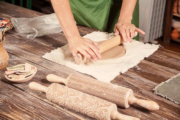 ポッターは茶色の粘土を転がす