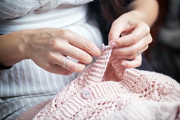 ボタンを縫う女性のクローズアップ