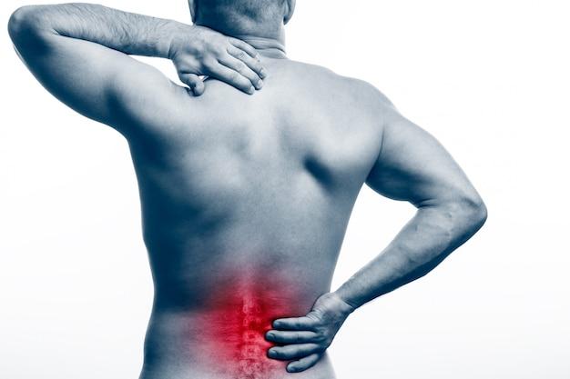 Молодой лысый человек спортивного телосложения держит больную спину