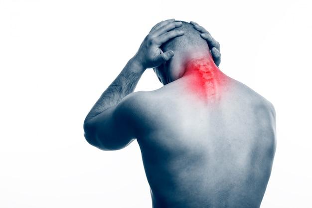 Молодой лысый мужчина спортивного телосложения держит больную шею