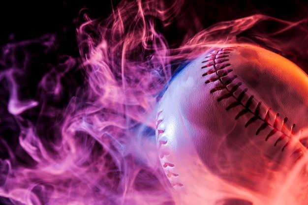 黒の孤立した背景にアークからのマルチカラーの赤い煙で白い野球ボールのクローズアップ