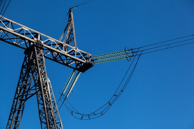 Сырой план металлический высоковольтный столб с большим количеством проводов на фоне голубого неба
