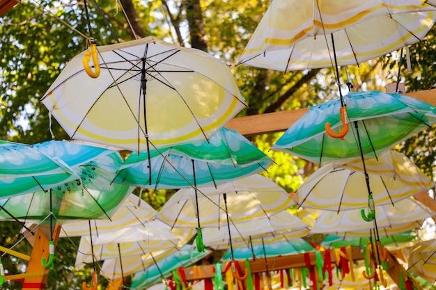Зонтики разных цветов в воздухе в парке.