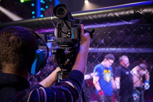 オペレーターはスポーツイベントでビデオを撮影します。仕事でプロのビデオ技術者。