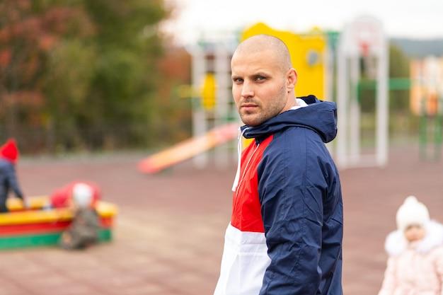 Молодой спортивный человек в спортивном костюме серьезно смотрит в камеру и гуляет по детской площадке в городском парке.