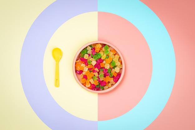 砂糖漬けのパイナップルの乾燥スライスと黄色ピンクの孤立した背景に黄色のスプーンでプラスチックのピンクプレート。