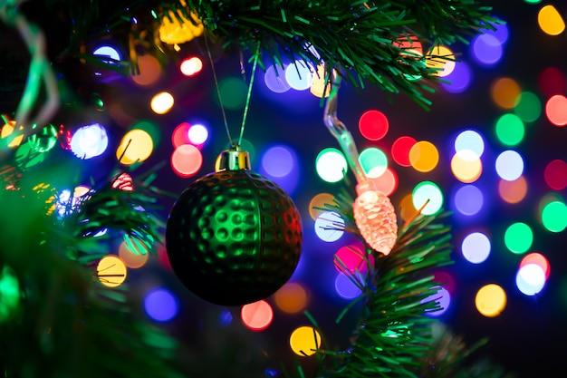 Зеленый блестящий елочный шар висит на елке, на заднем плане много гирлянд, светящихся в разные цвета.