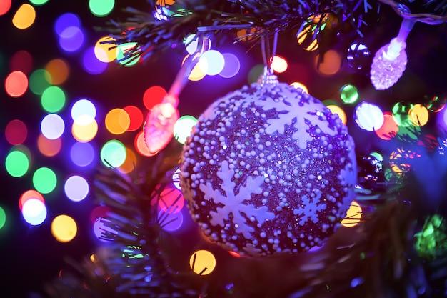 バックグラウンドでクリスマスツリーに掛かっているクリスマスボール異なる色で輝く花輪の多く。新年とクリスマスのコンセプト。