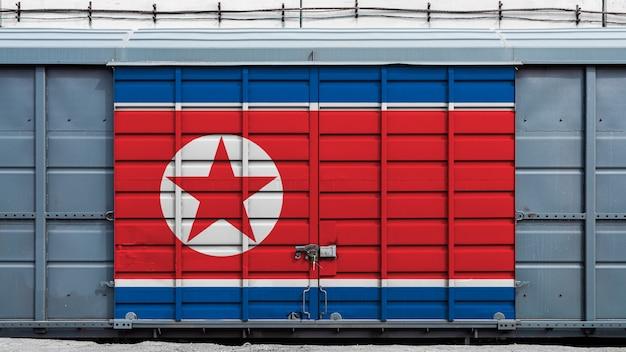 北朝鮮の国旗と大きな金属製のロックを備えたコンテナ列車貨物車の正面図。