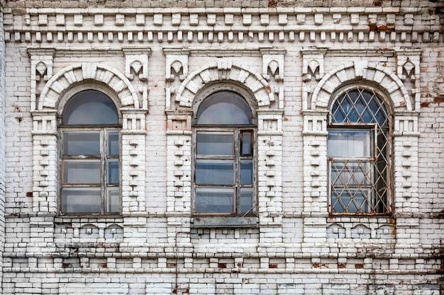 古い白いレンガで作られた大邸宅の古い木の木の古い窓のクローズアップ