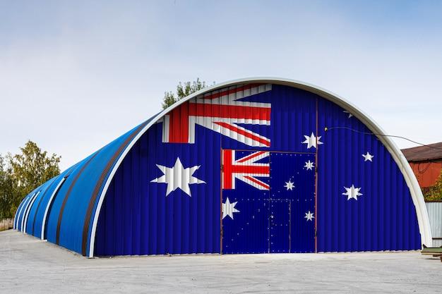 オーストラリアの国旗のクローズアップは、青い空を背景に閉じた領土の大きな倉庫の金属壁に描かれています。商品の保管、閉鎖エリアへの入場、物流の概念