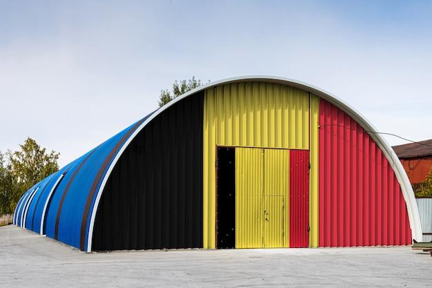 ベルギーの国旗のクローズアップは、青い空を背景に閉じた領土の大きな倉庫の金属壁に描かれました。商品の保管、閉鎖エリアへの入場、物流の概念