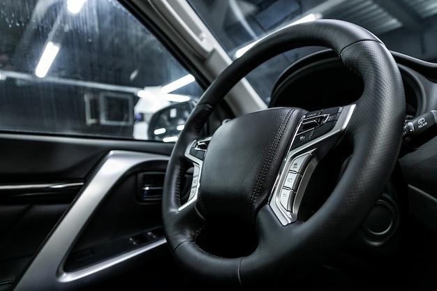 Крупный план приборной панели, плеера, руля, кнопок. современный интерьер автомобиля: детали, кнопки, ручки
