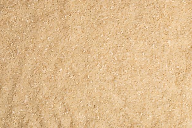 Конец-вверх сырых зерен белого риса. концепция здорового питания. сухой рис фон