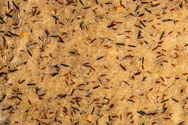 調理されていない白、黒、茶色の野生米粒のクローズアップ。健康食品のコンセプト。乾燥米の背景