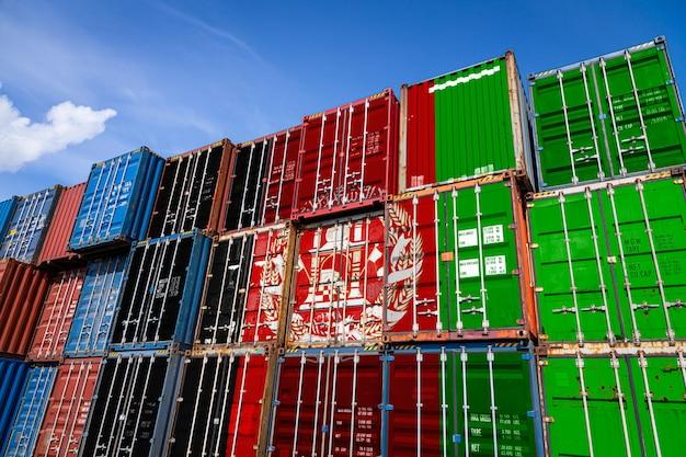 行に積み上げられた商品を保管するための多数の金属容器にアフガニスタンの国旗