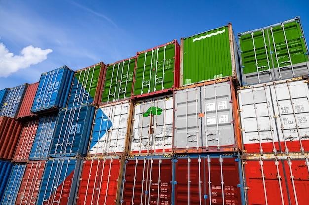 行に積み上げられた商品を保管するための多数の金属容器に赤道ギニアの国旗