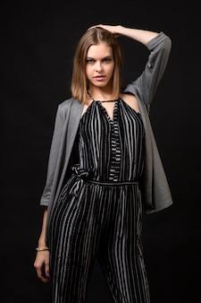 コンセプトビジネス女性。ストライプのオーバーオールとニットのオーバーオールでファッショナブルなビジネス服の魅力的な女性