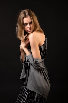 女性モデルがポーズを教えています。黒のオーバーオールとカーディガンのファッション性の高いモデルの女の子
