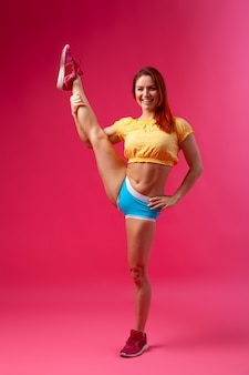 Красивая женщина с здорового тела носить в желтый топ и синие шорты на розовом