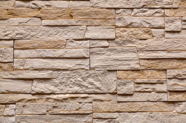 ブロックで作られた茶色の石の壁。スレート壁のテクスチャと背景のパターン