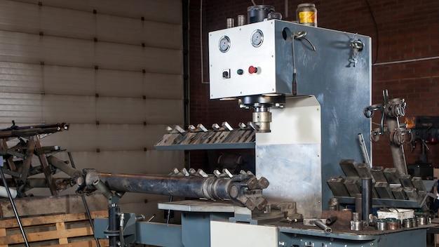 車やトラックを修理するための自動車整備士の職場:ワークショップでのカルダンシャフト、金属ハンマー、クランプ、スペアパーツの修理のための自動設置