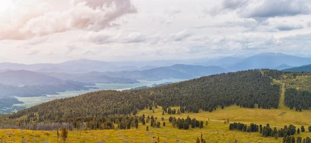 Осенний пейзаж горы алтая чемальского района: высокие горы, покрытые сосной и кедром, покрытые облаками. панорама гор.