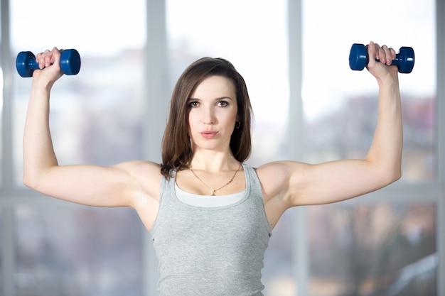 Спортивная молодая женщина, поднимающая гантели