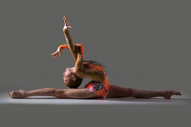Девушка-танцор сидит в расколах