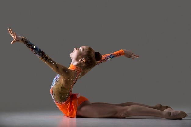 Девушка-танцор делает упражнения в гимнастике
