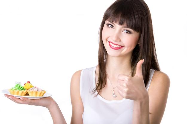 Молодая женщина, рекомендующая торты