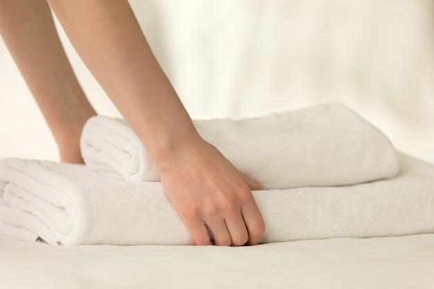 メイドはベッドにタオルのスタックを置く