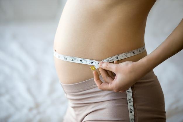 妊娠中の女性は彼女のウエストを測定する