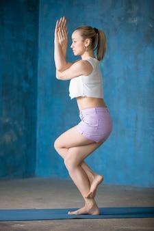 美しいスポーティーな若い女性ガルーダサナ姿勢をしている