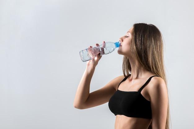 スポーツトレーニング後のスポーティな女の子の飲み水