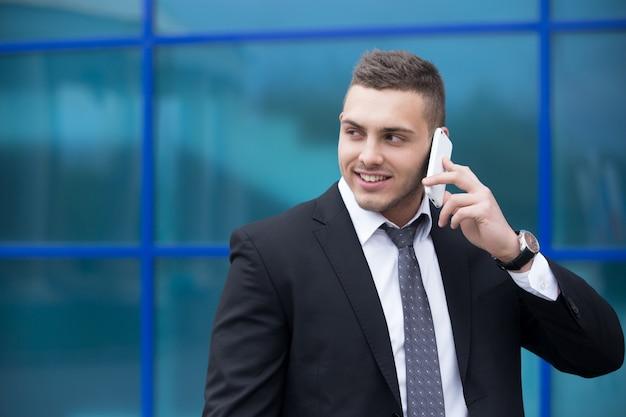 スマートフォンで幸せなビジネスマンの肖像画。スペースをコピーする