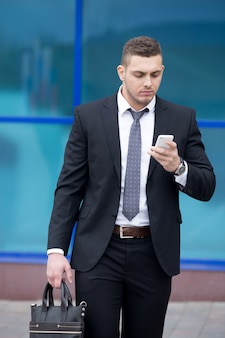 Портрет деловой человек, глядя на экран смартфона с сосредоточенным выражением