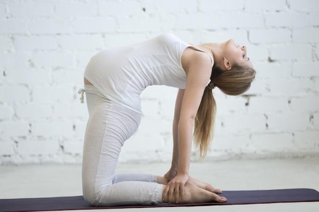 Беременная молодая женщина делает пренатальную йогу. поцелуй верблюда