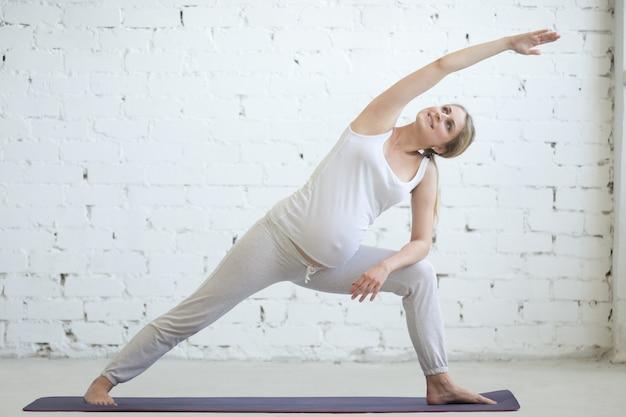 Беременная молодая женщина делает пренатальную йогу. уттита парсваконасана позирует