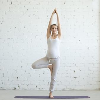 Беременная молодая женщина делает пренатальную йогу. врксасана поза