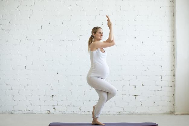 妊婦のヨガをやっている妊娠中の若い女性。イーグルポーズ