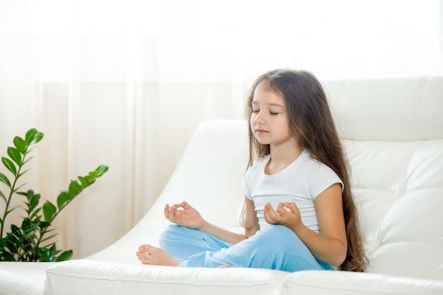 家でヨガをやっている幸せな子供の女の子