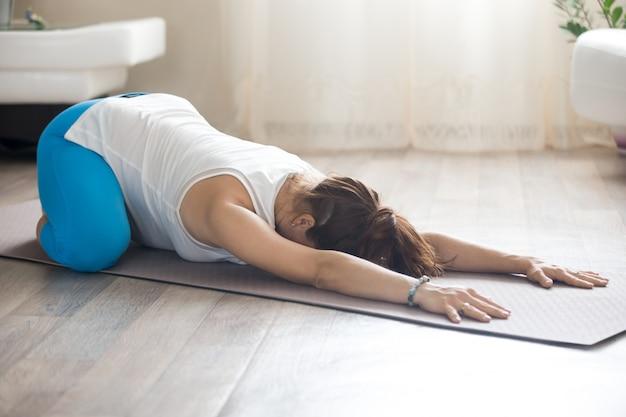 Беременная женщина делает предродовую детскую йогую позу дома