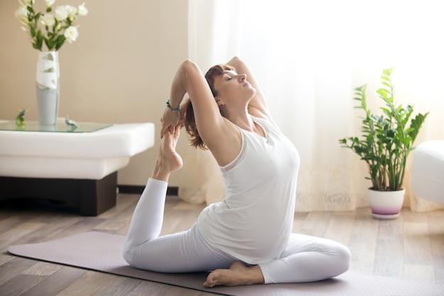 Беременная женщина делает одноногий голубь йога позирует дома