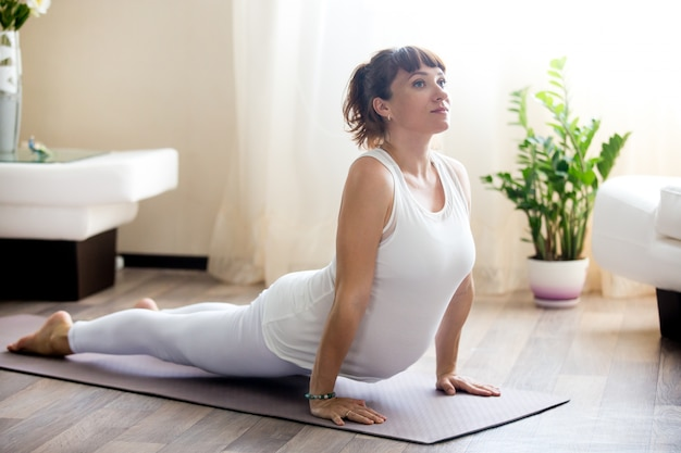 Беременная женщина делает восходящую сторону собака йога позирует дома